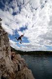 Risktaker. A young man jumps from a cliff into the sea Royalty Free Stock Image