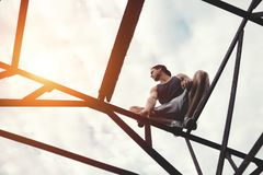 Risky brave man balancing and sitting on high metal construction royalty free stock images