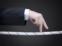 Risky business. Close up of a businessman's fingers walking on the tightrope. Conceptual image Royalty Free Stock Photo