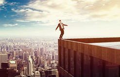 Risky Business. Man balancing on a high rise roof Stock Photography