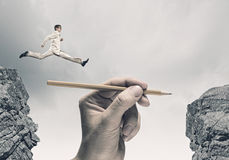 Risky business. Young businessman jumping over gap. Risk concept Royalty Free Stock Image