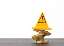 Risky coin stack and Warning label on white background.Financial. Crisis concept Royalty Free Stock Photos