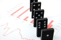 Risky domino over a financial business chart Stock Photos