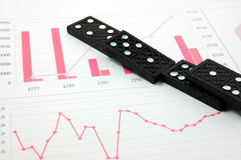 Risky domino over a financial business chart Stock Photo