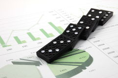 Risky domino over a financial business chart stock image