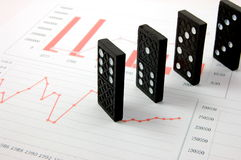 Risky domino over a financial business chart Royalty Free Stock Photos