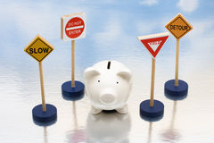 Risky Investments. Piggy bank sitting next to a road signs, risky investments Royalty Free Stock Photo