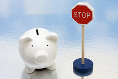 Risky Investments. Piggy bank sitting next to a red stop sign, risky investments Stock Images