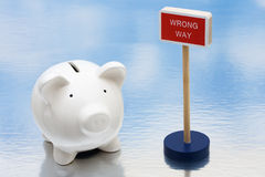 Risky Investments. Piggy bank sitting next to a red wrong way sign, risky investments Stock Images