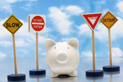 Risky Investments. Piggy bank sitting next to a road signs on a sky background, risky investments Stock Photography