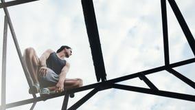 Risky man balancing and sitting on high metal construction. Outdoors Stock Photos