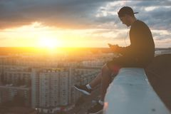 Risky man sitting on the edge of the roof with smartphone and listening music. Outdoors Stock Photo