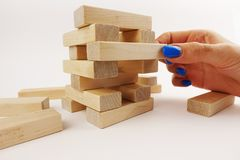 Risky moves concept with woman hand tacking an wooden piece from a tower Stock Image