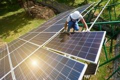 Risky work: mounting solar batteries on green metallic carcass. stock image