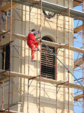 Risky worker. A worker climbing up the church tower structure without helmet or safety rope Stock Photo