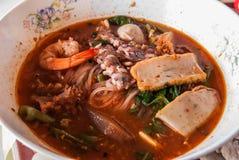 Risnoddle med havs- toppning i röd kryddig soppa Arkivfoton