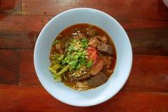 Risnudlar blandar med kryddig grisköttsås, och grönsaker tjänar som i blåttbunke Fotografering för Bildbyråer