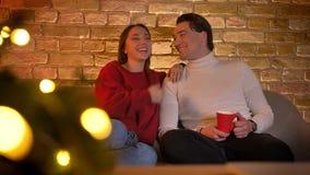 Riso abraçando os pares caucasianos que sentam-se no sofá e olhando o filme com o copo da bebida na atmosfera de casa confortável filme