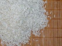 Riso bianco crudo sulla stuoia di legno Fotografie Stock