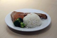 Riso bianco della bistecca di braciola di maiale e broccoli verdi nel piatto sulla tavola di legno immagine stock libera da diritti
