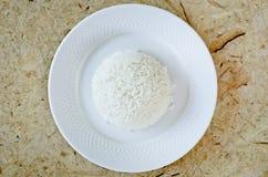 Riso bollito su un piatto bianco su fondo di legno Fotografia Stock