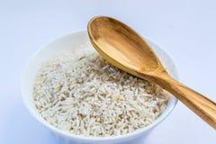 Riso crudo in piatto bianco e cucchiaio di legno Immagine Stock