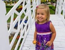 Riso da menina vai sobre a ponte branca Foto de Stock