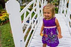 Riso da menina vai sobre a ponte branca Imagens de Stock Royalty Free