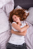 Riso de encontro da mulher ruivo nova em sua cama Fotos de Stock