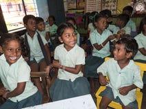 Riso de sorriso engraçado feliz dos colegas das meninas e dos meninos dos amigos das crianças na sala de aula na escola imagem de stock royalty free