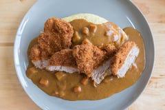 Riso dell'omelette con curry giapponese e Fried Pork Cutlet profondo impanato sulla Tabella di legno moderna Fotografia Stock