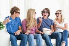 Riso dos amigos ao redor ao prestar atenção a um filme Fotografia de Stock