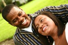 Riso dos pares do americano africano ao ar livre imagens de stock