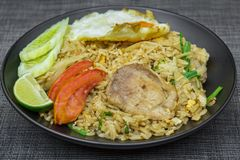 Riso fritto con carne di maiale, calce, la patata, i cetrioli e l'uovo fritto in b Immagini Stock Libere da Diritti