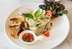 Riso fritto decorativo con il pesce croccante sul piatto bianco Fotografia Stock Libera da Diritti