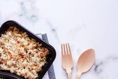 Riso fritto delizioso in scatola di pranzo con la biancheria da tavola, il cucchiaio di legno e la forchetta su fondo di marmo fotografia stock libera da diritti