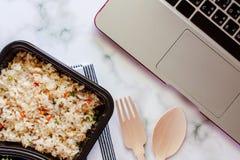 Riso fritto delizioso in scatola di pranzo sulla biancheria da tavola con il cucchiaio ed il computer portatile di legno del comp fotografia stock