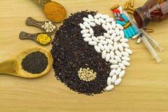 Riso nero e pillola bianca che formano un simbolo e un turmer di yin yang Fotografie Stock Libere da Diritti
