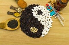 Riso nero e pillola bianca che formano un simbolo e un turmer di yin yang Immagini Stock