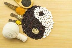 Riso nero e pillola bianca che formano un simbolo e una stazione termale di yin yang di erbe Fotografia Stock Libera da Diritti