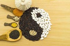 Riso nero e pillola bianca che formano un simbolo e una stazione termale di yin yang di erbe Fotografie Stock
