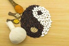 Riso nero e pillola bianca che formano un simbolo e una stazione termale di yin yang di erbe Immagine Stock Libera da Diritti