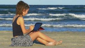 Riso novo da fêmea duro ao ter a sessão engraçada do bate-papo em seu PC da tabuleta na praia video estoque