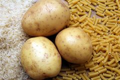 Riso, patate e pasta dei maccheroni su una tavola di legno Tre carboidrati comuni che forniscono l'energia ma possono causare l'o Fotografia Stock