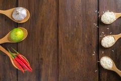 Riso, peperoncini rossi rossi, aglio e limone su fondo di legno fotografia stock