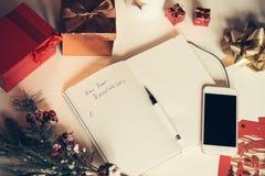 Risoluzioni del nuovo anno scritte sul taccuino con le decorazioni dei nuovi anni Fotografie Stock Libere da Diritti
