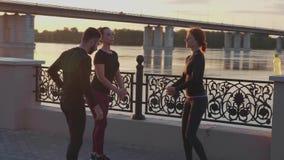 Risolvere della gente Uomo e donna che fanno allungando esercizio contro un bello tramonto stock footage