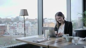 Risos da jovem mulher, sentando-se na cafetaria na tabela de madeira Na tabela é o portátil de alumínio cinzento Menina que publi filme