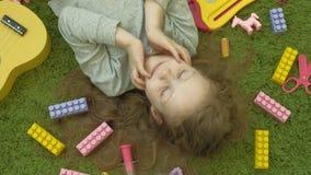 Risos da menina que encontram-se no fundo verde, vista superior filme