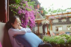 Risos da menina que sentam-se no sofá exterior Imagem de Stock Royalty Free